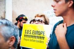 Белая женщина держит знамя для иммигрантов на для гостеприимстве на марше для беженцев Рима, Италии, 11-ое сентября 2015 Стоковое Изображение