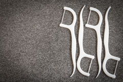 Белая зубоврачебная зубочистка на предпосылке ткани стоковые изображения