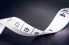 Белая измеряя лента на темной предпосылке Свернутая лента с номерами Стоковое Фото