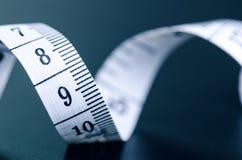 Белая измеряя лента на темной предпосылке Свернутая лента с номерами Стоковые Фотографии RF