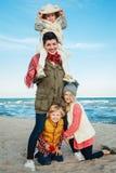белая кавказская семья, мать с 3 детьми ягнится обнимать усмехаясь смеяться над на пляже моря океана на заходе солнца outdoors Стоковые Изображения