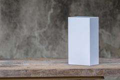 Белая картонная коробка на деревянном столе Стоковые Изображения RF