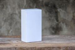 Белая картонная коробка на деревянном столе Стоковые Фотографии RF