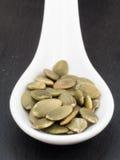 Белая керамическая ложка с семенами тыквы Стоковое фото RF