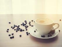 Белая кофейная чашка кофе latte и кофейного зерна, теплого тона Стоковое Изображение