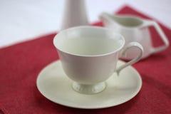 белая кофейная чашка на красной предпосылке Стоковое фото RF