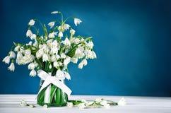Белая красивая стойка лилии Loddon цветков в стеклянной вазе на белых деревянных досках Стоковые Фото