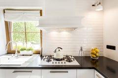 Белая кухня с черным countertop Стоковое Фото