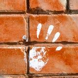 Белая печать краски правой руки на красной кирпичной стене Стоковая Фотография RF