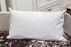 Белая поясничная подушка на кровати, модель-макет случая внутреннее фото стоковое изображение