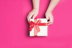 Белая подарочная коробка с красным смычком в руках ` s детей на розовом backgroundclose вверх Стоковые Изображения