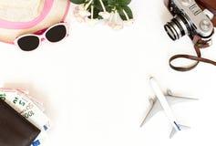 Белая предпосылка, перемещение, самолет, камера, соломенная шляпа, портмоне с карточками банка и деньги, взгляд сверху Стоковое фото RF