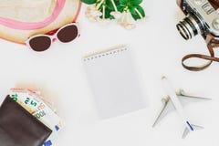 Белая предпосылка, перемещение, самолет, камера, соломенная шляпа, портмоне с карточками банка и деньги, тетрадь, взгляд сверху Стоковое фото RF