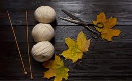 Белая пряжа, деревянные вязать иглы, ножницы, желтый цвет выходит К Стоковая Фотография RF