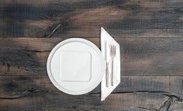 Белая плита, нож, вилка, салфетка Предпосылка пустых блюд деревянная Стоковая Фотография RF