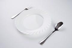 Белая плита с серебряной вилкой и ложка изолированная на белой предпосылке с космосом экземпляра Установка места обеда Поставьте  Стоковые Фото