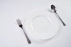 Белая плита с серебряной вилкой и ложка изолированная на белой предпосылке с космосом экземпляра Установка места обеда Поставьте  Стоковая Фотография RF