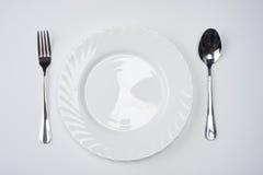 Белая плита с серебряной вилкой и ложка изолированная на белой предпосылке с космосом экземпляра Установка места обеда Поставьте  Стоковое Фото