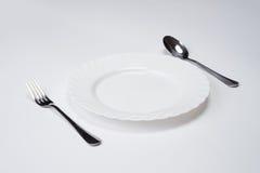 Белая плита с серебряной вилкой и ложка изолированная на белой предпосылке с космосом экземпляра Установка места обеда Поставьте  Стоковое Изображение