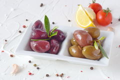 Белая плита с черными и зелеными оливками с прованскими листьями на белой абстрактной предпосылке с лимоном, томатом вишни Стоковое фото RF