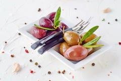 Белая плита с черными и зелеными оливками с прованскими листьями на белой абстрактной предпосылке с лимоном, томатом вишни Стоковые Фото