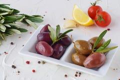 Белая плита с черными и зелеными оливками с прованскими листьями на белой абстрактной предпосылке с лимоном, томатом вишни Стоковое Изображение RF