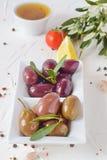 Белая плита с черными и зелеными оливками с прованскими листьями на белой абстрактной предпосылке с лимоном, томатом вишни Стоковая Фотография