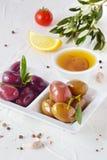 Белая плита с черными и зелеными оливками с прованскими листьями на белой абстрактной предпосылке с лимоном, томатом вишни Стоковые Изображения