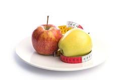 Белая плита с яблоком и измеряя лента на белизне Стоковое Изображение