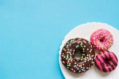 Белая плита с donuts на голубой предпосылке Стоковое Изображение