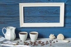 Белая рамка, 2 кофейной чашки и кувшин на предпосылке голубого b Стоковое фото RF