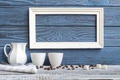 Белая рамка, 2 кофейной чашки и кувшин на предпосылке голубого b Стоковые Фото