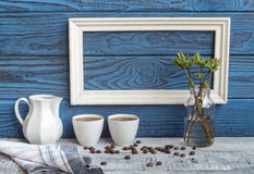 Белая рамка, 2 кофейной чашки и кувшин на предпосылке голубого b Стоковые Фотографии RF