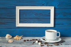 Белая рамка, 2 кофейной чашки и кувшин на предпосылке голубого b Стоковые Изображения