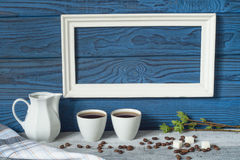 Белая рамка, 2 кофейной чашки и кувшин на предпосылке голубого b Стоковое Фото