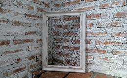 Белая рамка на стене выставки кирпича под светом через крышу под ярким солнечным светом Стоковое Изображение RF