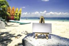 Белая рамка холста и деревянная тренога на тропическом пляже Стоковые Изображения