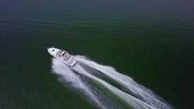Белая роскошная моторная лодка яхты плавая прочь медленно в спокойном темносинем seascape речной воды в изумлять воздушный взгляд видеоматериал