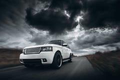 Белая скорость автомобиля управляя на дороге на драматическом дневном времени облаков Стоковые Изображения
