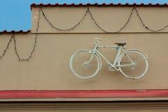Белая смертная казнь через повешение велосипеда на стене дома около крыши Стоковое фото RF