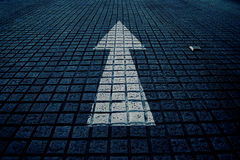 Белая стрелка вперед на голубой улице блока, винтажном голубом тоне Стоковое фото RF