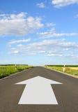 Белая стрелка на дезертированной дороге Стоковые Фото
