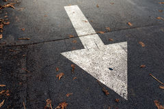 Белая стрелка на дороге асфальта, знаке уличного движения стоковые изображения rf