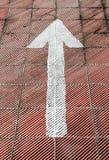 Белая стрелка покрашенная на поле автостоянки Стоковая Фотография RF