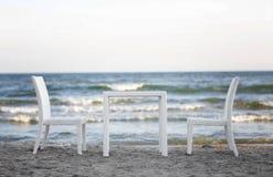 Белая таблица и 2 удобных стуль на красивой предпосылке моря Романтичная атмосфера на пляже Мебель на природе Стоковые Изображения RF
