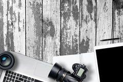 Белая таблица стола фотографии офиса с компьтер-книжкой, таблеткой, камерой и стеклом на деревянном backgroung Взгляд сверху с ко стоковые изображения