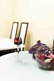 Белая таблица с бокалом вина и цветками Стоковые Изображения RF