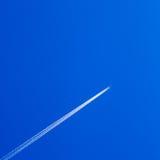 Белая трассировка конденсационного следа самолета на голубом небе Стоковые Фотографии RF