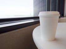 Белая устранимая кофейная чашка на таблице Стоковая Фотография