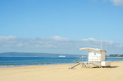 Белая хата на песчаном пляже, сейф спасения ослабляет океаном, быть Стоковые Изображения RF